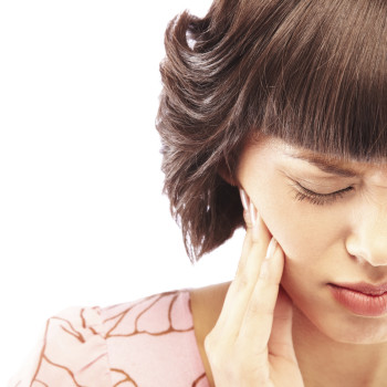 Close-up of a woman having toothache isolated on white background